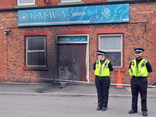 Officers standing guard outside theJamia Masjid Abu Huraira Mosque in Beeston following yesterday's arson attack. Picture: Gary Longbottom
