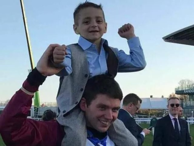 Bradley Lowery is held aloft by Grand National-winning jockey Derek Fox