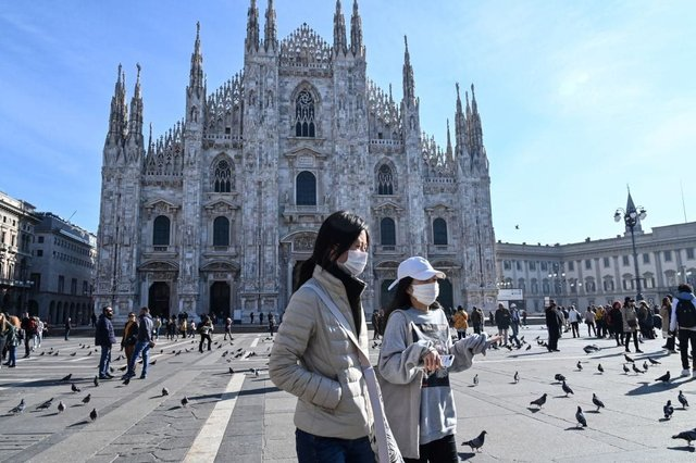 Two women wearing a protective facemask walk across the Piazza del Duomo, in front of the Duomo, in central Milan, on February 24, 2020