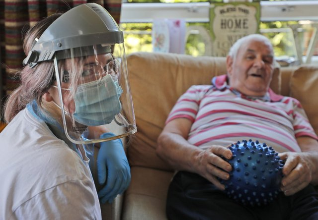 A nurse in PPE (personal protective equipment) speaks to a care home as the Government stands accused of neglecting social care.