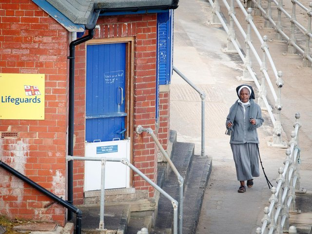 A woman walks along the sea front in Whitby, Yorkshire , after the introduction of measures to bring the country out of lockdown. Photo: PA