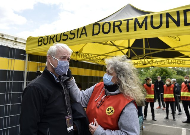 A TV crew member has his temperature checked before entering the stadium for the German Bundesliga soccer match between Borussia Dortmund and Schalke 04 in Dortmund, Germany. PA Photo. Picture date: Saturday May 16, 2020. Erling Haaland carried on where he left off before the coronavirus suspension as the teenager kicked off Borussia Dortmund's thumping victory against rivals Schalke 04 in an entertaining, if surreal, return to Bundesliga action.