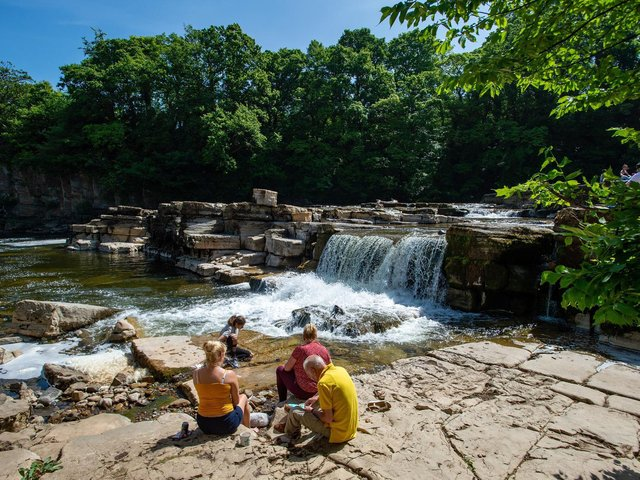 People enjoying the warm weather beside the River Swale at Richmond Falls. Picture Bruce Rollinson