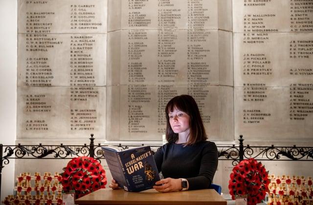 Lindsey Davis, development director at Bradford Grammar School reads the newbook dedicated to Old Bradfordian Harry Rée