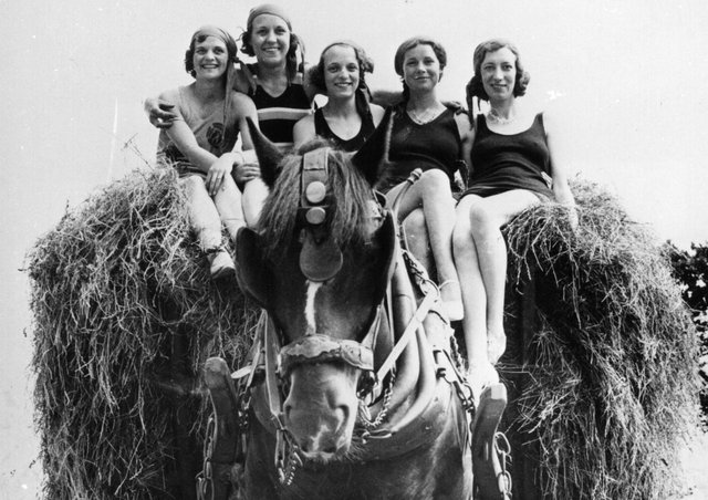 30th June 1934:  Girls in bathing costumes ride home on a load of hay after helping out with the harvest, at Torquay.  (Photo by Fox Photos/Getty Images)