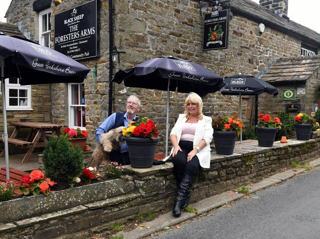Keith and Lesley Sharpe with Barney the dog outside The Foresters Arms at Carlton in Coverdale.