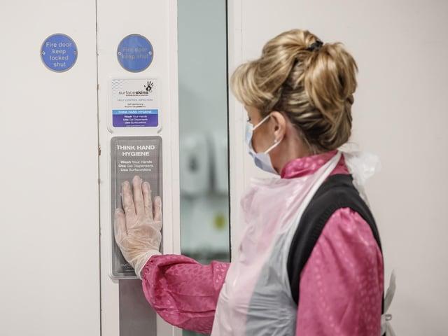 Vida Grange employee Debs Bannister uses a Surfaceskins self-disinfecting door pad