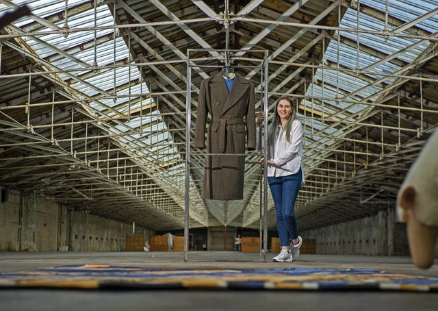 Emma Herst with her coat on display at Salts Mill, Bradford.The University of Huddersfield student has won a Wool Week 2020 competition to design a cloth to make an overcoat, woven by Abraham Moon, inspired by one Prince Charles has worn since the 1970s. Picture Tony Johnson