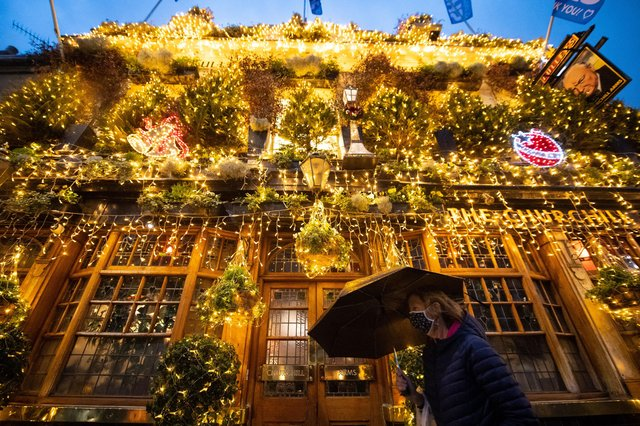 A woman in a face mask walks past Christmas lights outside a closed pub