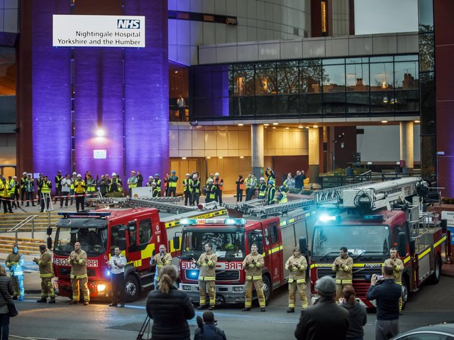Members of the fire brigade, construction workers and members of the public, clapping outside the Nightingale Hospital at the Harrogate Convention Centre in Harrogate