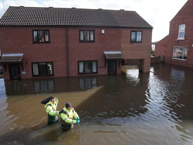 Rescue workers wade through water in the flooded village of East Cowick, Yorkshire, after Storm Jorge battered the UK