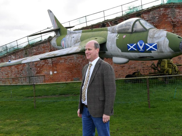 Auctioneer Andrew Baitson standing by the aircraft at Fort Paull near Hull Picture: Jonathan Gawthorpe