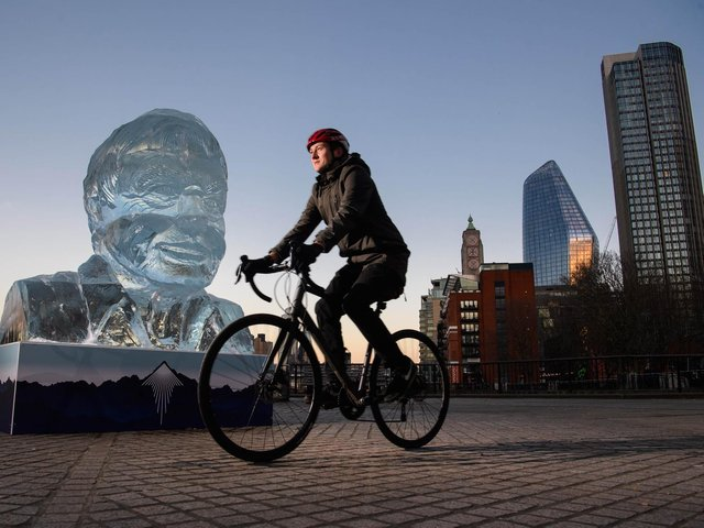 Library image of a cyclist riding past an ice-sculpture of Sir David Attenborough