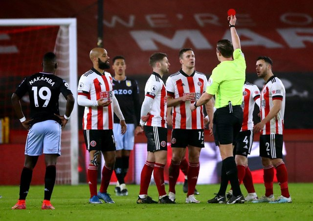 Sheffield United's Phil Jagielka (centre right) sees his yellow card upgraded to a red card after referee Robert Jones consults the VAR. Picture: PA