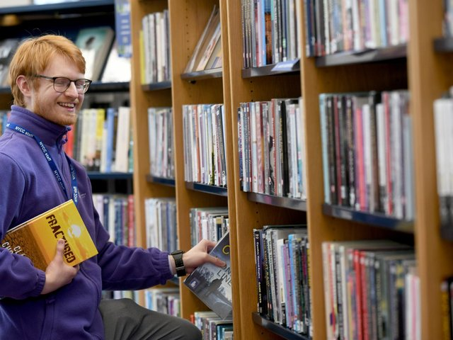 Joe Atkinson Library Assistant at Harrogate Library arranging the large print books. Image by Gary Longbottom.