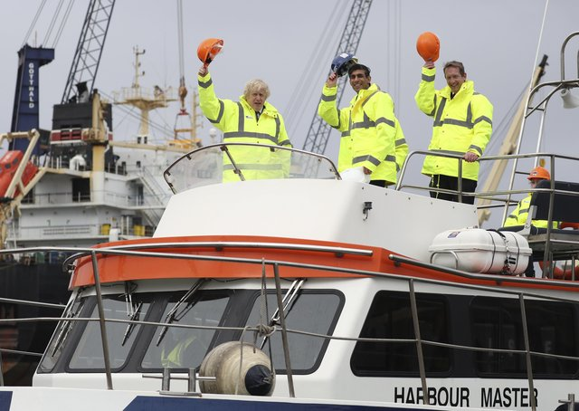 Boris Johnson (L) and Chancellor of the Exchequer Rishi Sunak (C), stand on board a boat on the River Tees on March 4, 2021 in Teesport, England. Teesport has been chosen as one of eight sites for new Freeports in England.