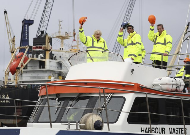 Prime Minister Boris Johnson (L) and Chancellor of the Exchequer Rishi Sunak (C), stand on board a boat on the River Tees on March 4, 2021 in Teesport, England. Teesport has been chosen as one of eight sites for new Freeports.