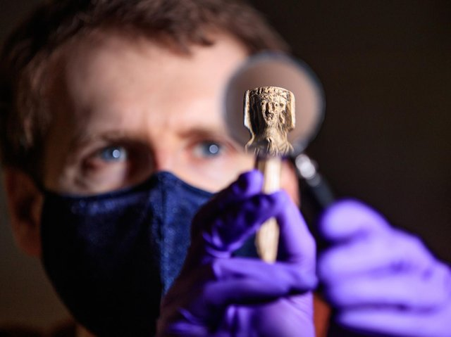 Andrew Woods, senior curator at the Yorkshire Museum, holds a magnifying glass in front of a medieval bone handle carving of a woman dressed in a gown and headdress, dating to the 14th Century