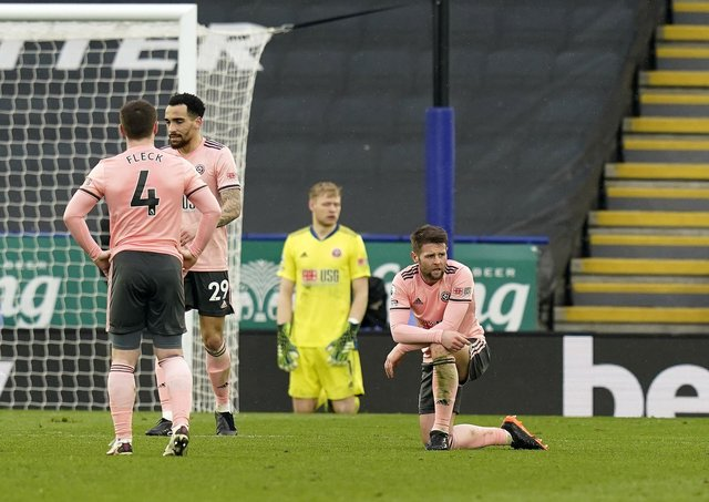 On their knees: Oliver Norwood and his Blades team-mates  look dejected after going 4-0 down against Leicester City. Picture: Andrew Yates/Sportimage