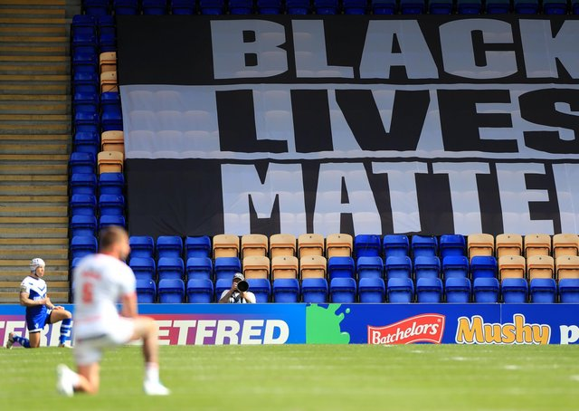A Black Lives Matter banner as players take a knee in support of the movement during a Betfred Super League match last season.