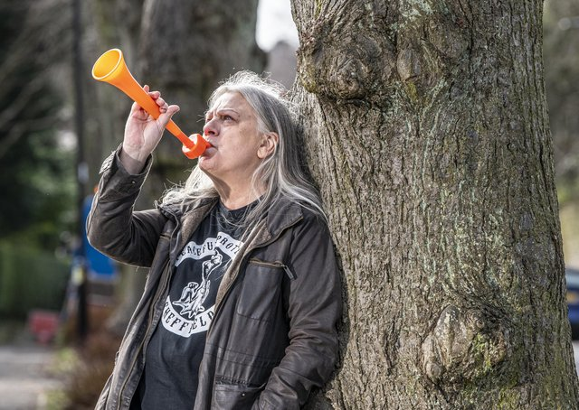 Sheffield trees campaigner Andrea Stone by the tree in the road which was saved. In March 2018 she went viral for being arrested for blowing a toy trumpet at a Sheffield trees protest.  Picture Tony Johnson