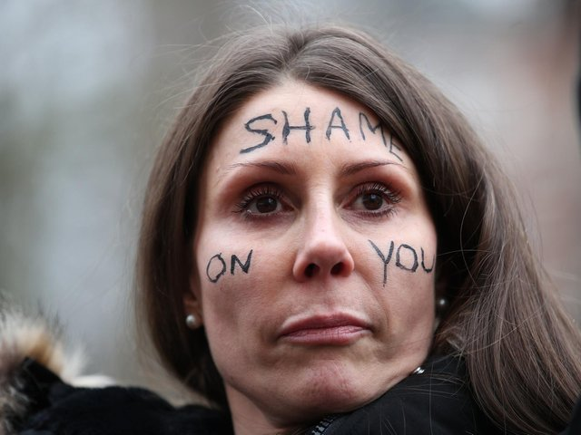 A woman with the words 'Shame on you' written on her face stands outside New Scotland Yard in London. Picture: Yui Mok