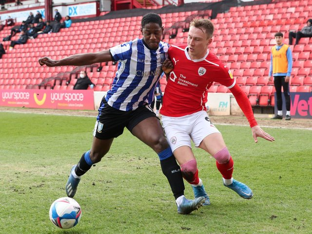 Sheffield Wednesday defender Osaze Urhoghide shields the ball ahead of Barnsley's Cauley Woodrow. Picture: PA.