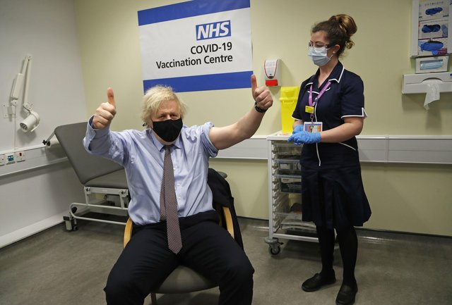 Prime Minister Boris Johnson gives thumbs up after receiving the first dose of AstraZeneca vaccine administered by nurse and Clinical Pod Lead, Lily Harrington at Westminster Bridge Vaccination Centre at St Thomas' Hospital in London. Picture: Frank Augstein/PA Wire