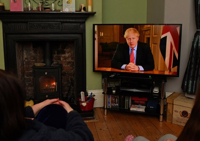 Members of a family listen as Britain's Prime Minister Boris Johnson makes a televised address to the nation from inside 10 Downing Street in London, with the latest instructions to stay at home to help contain the Covid-19 pandemic, from a house in Liverpool on March 23, 2020.(Photo by PAUL ELLIS/AFP via Getty Images)