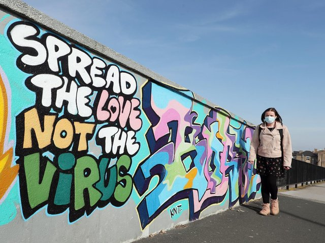 """A woman walks past street art that reads """"Spread the love not the virus"""" in Hull during England's third national lockdown to curb the spread of coronavirus."""