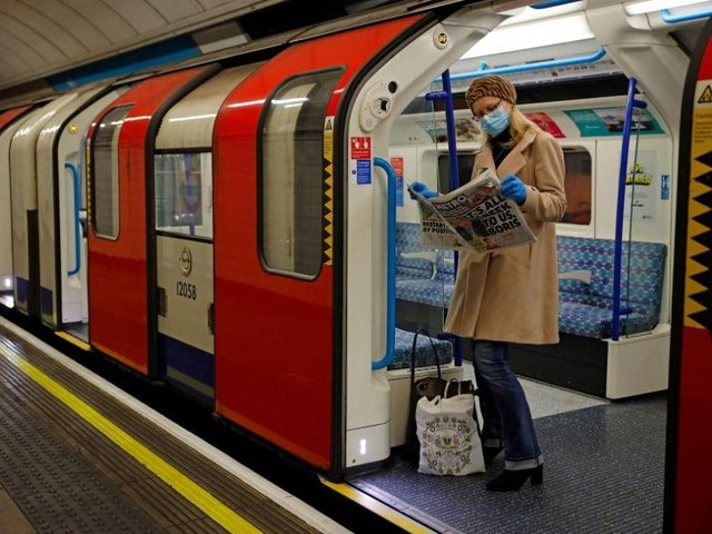 A woman reads a newspaper on the London Underground. Photo by TOLGA AKMEN/AFP via Getty Images.