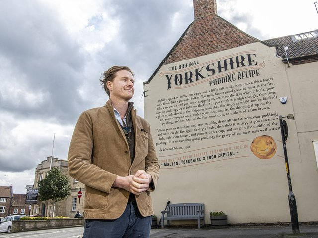 Tom Naylor-Leyland, who is the organiser of the Malton Food Festival, in front of the large mural of a Yorkshire pudding recipe dating from the 18th century which was created a couple of years ago on the side of McClaren's solicitors on Newgate