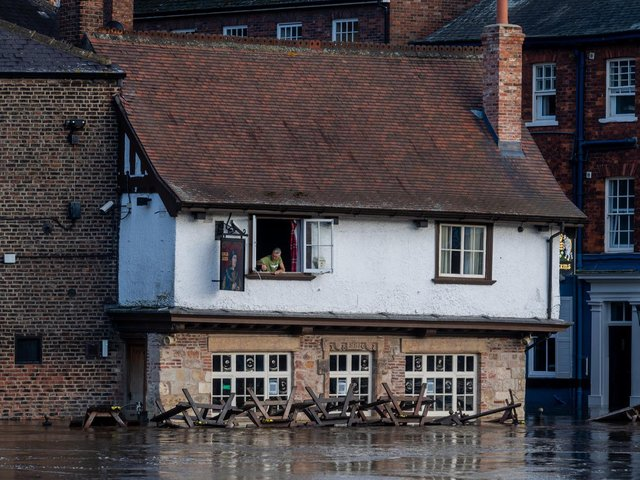 Colin Fidler, Landlord of the Kings Arms, King's Staith, York, peers from his upstairs window as rising floodwater from the River Ouse is pumped out of his pub Credit: James Hardisty