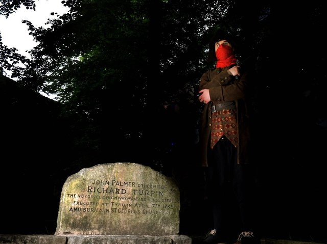 Simon Ahaimi from York Dungeon dressed as Dick Turpin in St George's Graveyard in York where the grave of Richard Turpin lies.