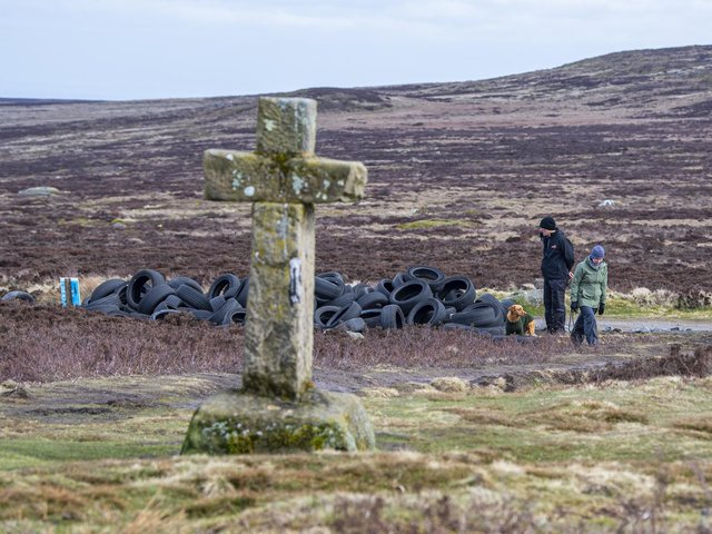 Dog walkers examine the pile of tyres dumped on Ilkley Moor