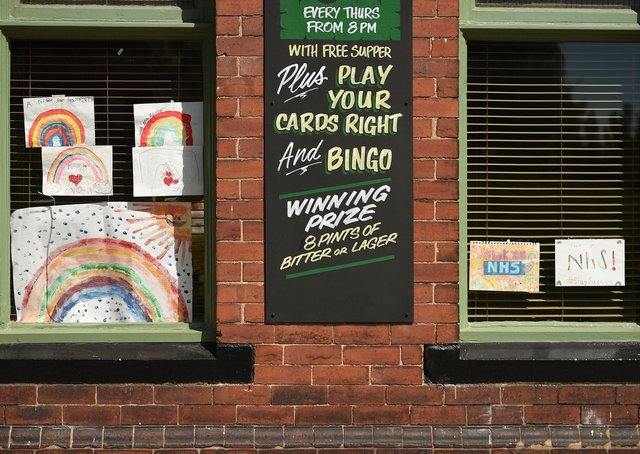 Posters depicting the colours of a rainbow, being used as symbols of hope during the COVID-19 pandemic, and paying tribute to Britain's NHS  workers, are seen in the window of a closed-down pub in  Pontefract.
