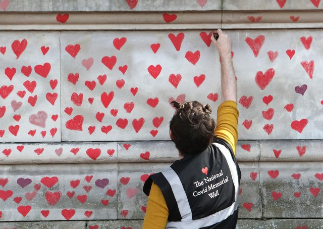 A volunteer paints hearts on the National Covid Memorial Wall on the Embankment, central London, which is being painted in memory of all those who have died from Covid.