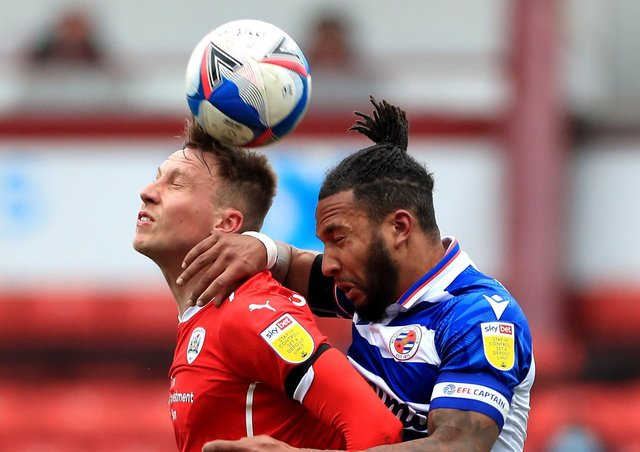 Barnsley's Cauley Woodrow (left) and Reading's Liam Moore battle for the ball. Pictures: PA