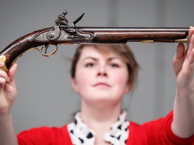 Alice Fitton holds a flintlock pistol once owned by William Rivers