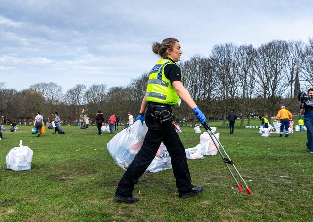 Police help clear litter in a Leeds park after the easing of the lockdown.