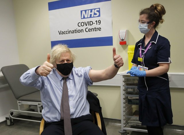 Prime Minister Boris Johnson gives thumbs up after receiving the first dose of AstraZeneca vaccine administered by nurse and Clinical Pod Lead, Lily Harrington at Westminster Bridge Vaccination Centre at St Thomas' Hospital in London where he was treated for Covid.