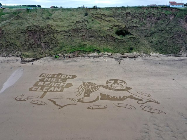 An aerial view of the 50-metre sand drawing created by Sand In Your Eye for Surfers Against Sewage's new Million Mile Beach Clean campaign, on Cayton Bay