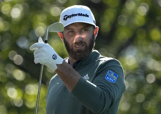Dustin Johnson selects a club on the fourth hole during a practice round for the Masters. Picture: AP/David J. Phillip
