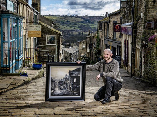 Danny Abrahams on Main Street in Haworth with a painting of the scene. (Tony Johnson).