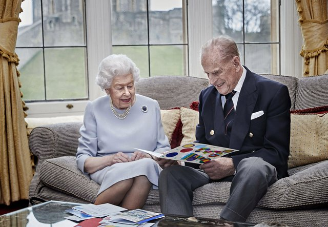 A touching photo of the Queen and Prince Philip on their 73rd wedding anniversary as they open a card from the Duke and Duchess of Cambridge's three children.