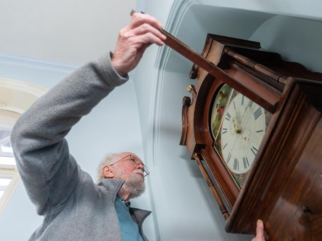 David Barker, a Fellow of the British Horological Institute (FBHI) and Accredited Conservator Restorer (ACR) checking the time on the grandfather clock