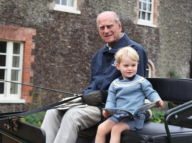 The Duke of Cambridge released a new photograph, taken by his wife, of a then two-year-old Prince George with his great-grandfather in one of his beloved carriages on the Sandringham Estate in Norfolk.