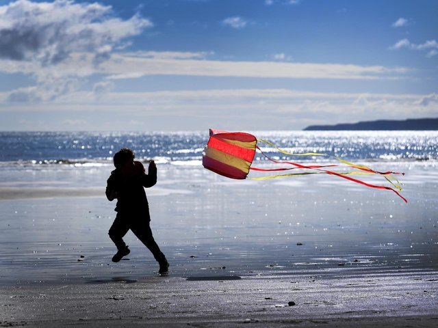 A child plays with a kite at the beach in Scarborough