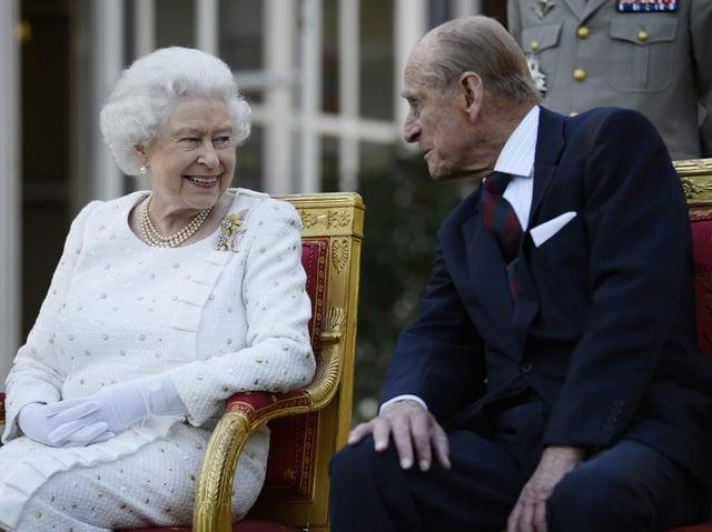 Queen Elizabeth II and the Duke of Edinburgh at a garden party in Paris