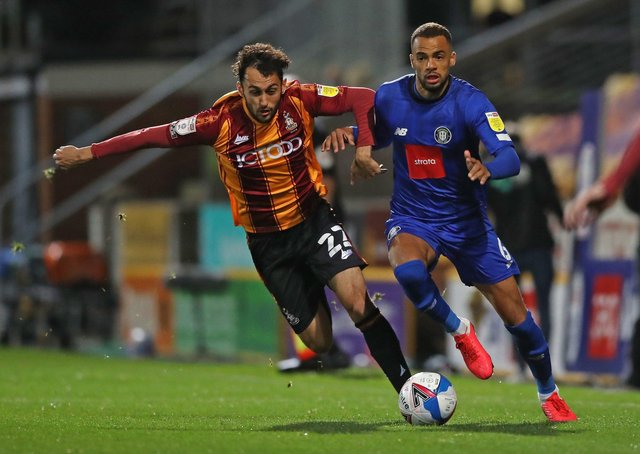 Bradford's Levi Sutton and Harrogate Town's Warren Burrell, right, battle for the ball back in October. Picture: PA